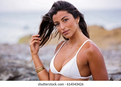 Beautiful, attractive young female model poses portrait style at the beach in a white bikini she has natural tanned skin and complexion. She is playing with her hair and smiling.