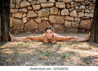 Beautiful attractive young fit woman in swimsuit doing stretching and splits between two trees,  Concept active vacation and harmony with surroundings