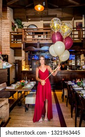 Beautiful, attractive young girl in red long dress with balloons in her hand, celebrating birthday in restaurant. Tables set in background