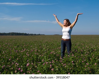 Beautiful attractive young happy woman girl in a sunny flowers field