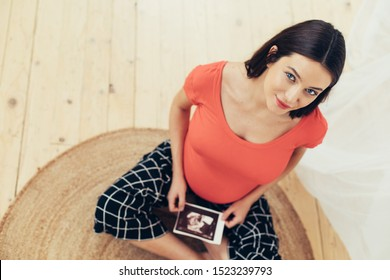 Beautiful attractive young pregnant woman sitting on floor and look up on camera. Hold ultrasonic picture in hand. Wear home clothes. Excited to become mother. Waiting for maternity time