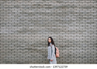 Beautiful attractive young woman with a backpack standing half a turn near the gray brick wall. Lonely look. Pensive girl. Gray colour. Copy space.