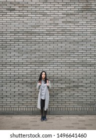 Beautiful attractive young woman with a backpack standing half a turn near the gray brick wall. Lonely look. Pensive girl. Copy space.