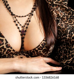 Beautiful attractive young woman in a dress  with large breasts and necklace on chest. Close-up view of the body part