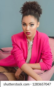 beautiful attractive young woman (mixed rase) with make up and in pink blazer sitiing on the chair