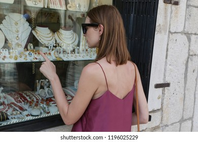 Beautiful attractive young woman near jewelry window shop