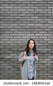 Beautiful attractive young woman with a pink backpack standing half a turn near the gray brick wall. Lonely look. Pensive girl. Gray colour.