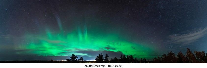Beautiful Aurora Borealis panorama photo across the whole horizon, above pine tree forest and city lights in Swedish countryside close to Umea city, Vasterbotten county. Ume river delta area.
