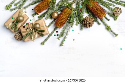 Beautiful Australian inspired Christmas composition. Native Banksia's with elegantly wrapped gifts, gold ribbon, decoration, pine cones and glitter one a white wooden background.