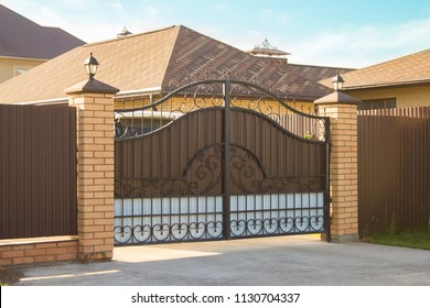 Beautiful automatic gate with forged elements in the family house