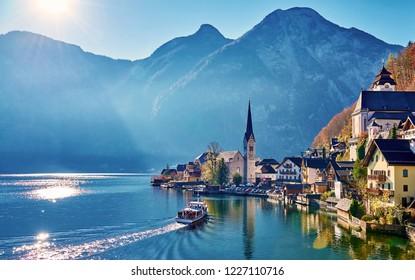Beautiful autum landscape of Hallstatt mountain village with Hallstatter lake and boat in Austrian Alps. Austria, Salzkammergut region.