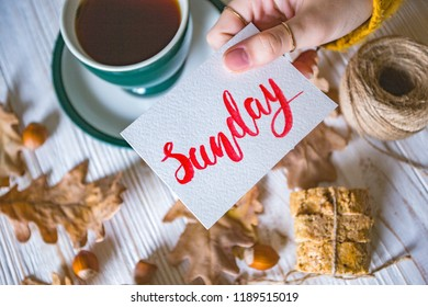 Beautiful autumn background - cup of tea, biscotti, autumn leaves and inscription Sunday