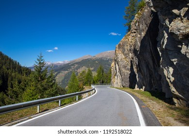 Beautiful autumn day on the Umbrail summit road in the Val Mustair, canton of Grisons in Switzerland. Tight curves on the mountain street. Street near by the rockface. Dangerous road.