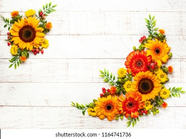 Beautiful autumn flowers and berries on the white wooden background. Top view with copy space. Autumnal concept.