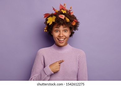 Beautiful autumn girl points at herself, glad being pick up to participate in seasonal festival, wears warm knitted sweater, colorful leaves, berries and flowers in hair, isolated on purple background