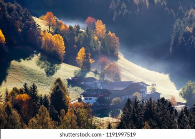Beautiful autumn landscape in the Alps with backlighted pasture, yellow and red trees, alpine farm buildings on misty meadow.