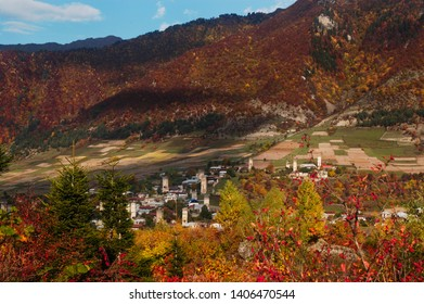 Beautiful autumn landscape with bright red, orange and yellow colours in Svaneti region,  Caucasus Mountains, Georgia. The town of Mestia with the traditional defensive towers in the background.