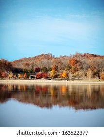 Beautiful autumn landscape with colorful trees, beach, and reflection in lake.