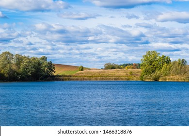 Beautiful autumn landscape with field, trees and deep clouds behind a lake