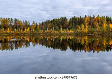 Beautiful autumn landscape with forest, lake and reflection, Finland