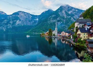 Beautiful autumn landscape of Hallstatt mountain village with Hallstatter lake and boat in Austrian Alps.