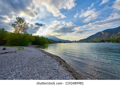 Beautiful autumn landscape with lake, mountains, forest, clouds and reflection in water. Austria, Salzkammergut, Wolfgangsee.