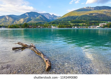 Beautiful autumn landscape with lake, mountains, forest, house, clouds and reflection in water. Austria, Salzkammergut, Wolfgangsee.