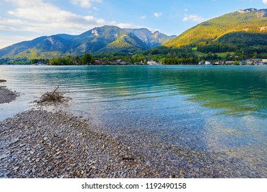 Beautiful autumn landscape with lake, mountains, forest, clouds, house and reflection in water. Austria, Salzkammergut, Wolfgangsee.