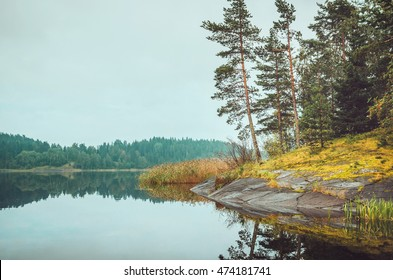 Beautiful autumn landscape with lake, pine trees, natural stone coast in the Republic of Karelia, Ladoga Lake, northern region in Russia. Fall forest, russian tourism and travel concept.