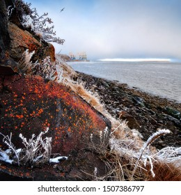 Beautiful autumn landscape with rocky coast and frost on the grass. In the distance the cranes of the sea port and fog. The stones are covered with lichen. Anadyr estuary, Chukotka, Far East of Russia