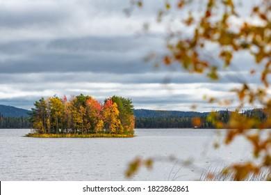 Beautiful autumn landscape with a small island on lake. Ruska season in Finland