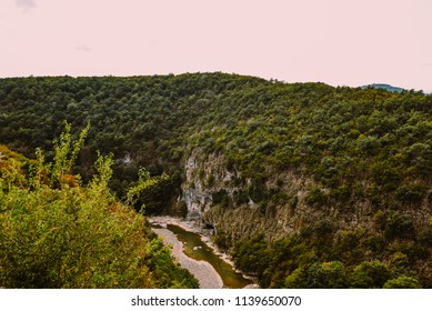 Beautiful autumn landscape with stream and forest. Landscape with mountains, high rocks, trees and cloudy sky. Rocky shore of mountain river in rainy autumn morning. Vintage toning. Travel background.