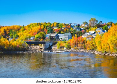 Beautiful autumn landscape view in Chicoutimi, Saguenay, Quebec City, Canada. A village on shore of lake with colorful trees, river and bridge against blue sky reflected in water during fall season.