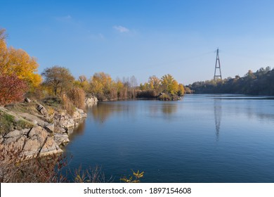 Beautiful autumn landscape. View of a lake in a quarry near the Kodak fortress and a power line pylon on a blue sky background.