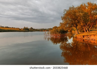 Beautiful autumn lanscape with trees reflection in water. Panorama of autumn evening lake. Tranquil evening view.