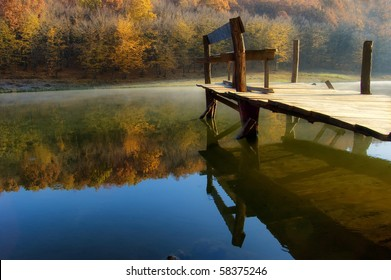 beautiful autumn morning at the lake near a colorful orange forest