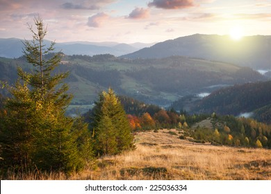 Beautiful Autumn in Mountains at sunset time. Colorful trees,  peaks, clouds and sun