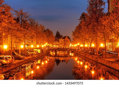 Beautiful autumn night scene in Leiden, The Netherlands still reflections in the canal water.