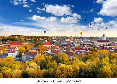 Beautiful autumn panorama of Vilnius old town with colorful hot air balloons in the sky, taken from the Gediminas hill