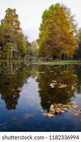 Beautiful autumn park with colorful trees and leaves and reflection in artificial ponds.