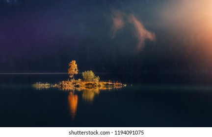 Beautiful autumn scene. Colorful foggy morning view of small island with trees under sunlit on lake, Magic atmothpheric landscape,  Amazing Nature background. Impressive Wild area. Creative Image.
