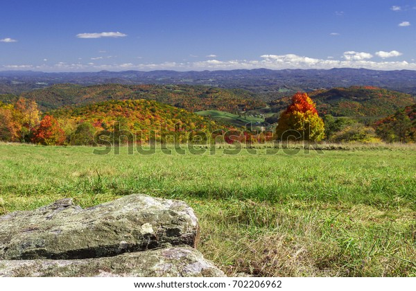 beautiful autumn scene looking from green field on a mountaintop over colorful trees