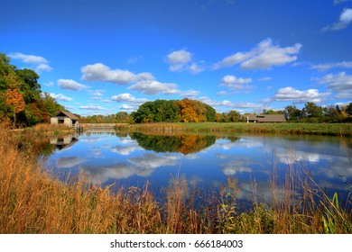 Beautiful autumn scene at a tranquil fishing pond in Ohio. The pond features a rustic shelter house.