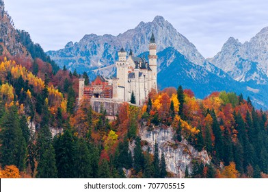 Beautiful autumn scenery of Neuschwanstein Castle with colorful autumn trees and the Alps on background. Bavaria, Germany.