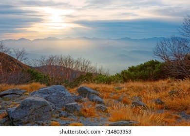 Beautiful autumn scenery of Senjojiki Cirque at sunrise with withered trees & grass by the mountainside and majestic foggy mountains in background in Japanese Central Alps Natural Park, Nagano, Japan