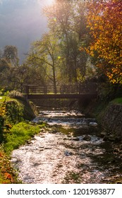 Beautiful autumn scenery, view of a wooden bridge over a river or creek in autumn with natural lens flare. Autumn river landscape background. Samobor near Zagreb in Croatia.