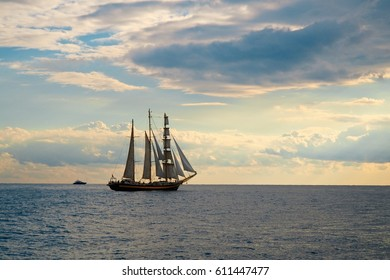 Beautiful autumn seascape with sail ship. Blue sky with clouds. Abstract seascape.