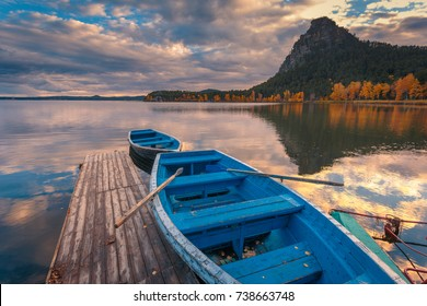 Beautiful autumn sunset landscape. Blue boats moored at wooden pier on the Borovoe lake at Burabay National park in Northern Kazakhstan.