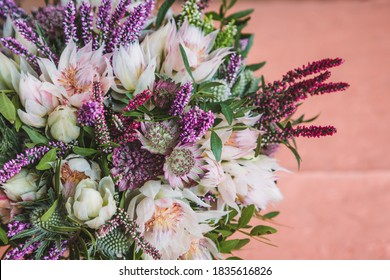Beautiful autumn, wedding bouquet made out of a sortiment of sessional flowers, such as Calluna Vulgaris, Astrantia, Eryngium and white blushing bride Protea
