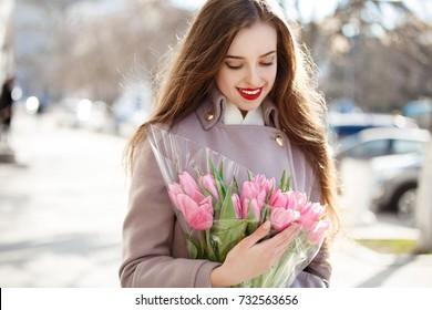 Beautiful autumn woman with flowers outdoors at street. Happy smiling girl with tulips bouquet wear autumn elegant coat and walking at city. Pretty young lady with flowers autumn outdoor portrait.